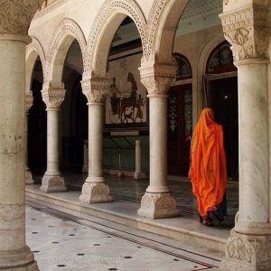 A colorfully veiled woman walks through a courtyard in the city of Jaipur, India.